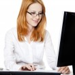 Smiling young business woman using computer — Stock Photo