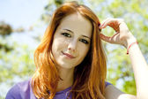 Beautiful redhead girl at the park in summer time. — Stock Photo