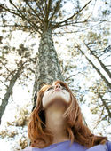 Beautiful redhead girl at the park in summer time looking up. — Stock Photo