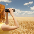 Redhead girl with binocular at wheat field. — Stock Photo #5961479