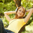 Redhead girl with headphones lie over tree at garden. — Stock Photo #5961534
