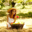 图库照片: Beautiful redhead girl with fruits in basket at garden.