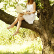 Redhead girl sitting at tree with notebook. — Stock Photo #5961670