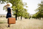 Lonely girl with suitcase at countryside. — Stock Photo