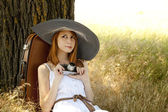 Redhead girl sitting near tree with vintage camera. — Stock Photo