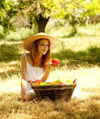 Beautiful redhead girl with fruits in basket at garden. — Photo