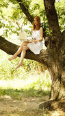 Redhead girl sitting at tree with notebook. — Stock Photo