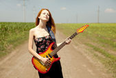 Rock girl with guitar at countryside. — Stock Photo