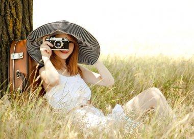 Redhead girl sitting near tree with vintage camera.