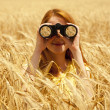 Redhead girl with binocular at wheat field. — Stock Photo #6024132