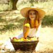 Beautiful redhead girl with fruits in basket at garden. — Stok Fotoğraf #6024333
