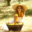 Beautiful redhead girl with fruits in basket at garden. — Photo #6024333