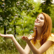 Royalty-Free Stock Photo: Redhead girl in the park under soap bubble rain.