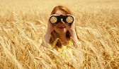 Redhead girl with binocular at wheat field. — Stock Photo