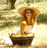 Beautiful redhead girl with fruits in basket at garden. — Stok fotoğraf