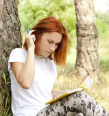 Redhead girl doing homework at outdoor. — Стоковое фото