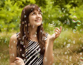 Brunette girl in the park under soap bubble rain. — Stock Photo