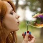 Redhead girl in the park under soap bubble rain. — Stock Photo