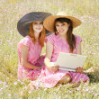 Two girls at contryside with notebook. — Stock Photo