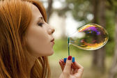 Redhead girl in the park under soap bubble rain. — Stock Photo