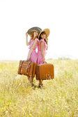Dvě dívky ve stylu retro s kufry v krajině. — Stock fotografie