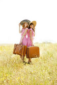 Two retro style girls with suitcases at countryside. — Stock Photo