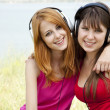 Stock Photo: Two teenage girls listening to MP3 player