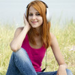 Redhead girl with headphone in the park. — Stockfoto