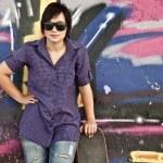Style girl with skateboard near graffiti wall. — Stock Photo #6124620