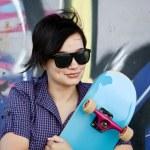 Style girl with skateboard near graffiti wall. — Stock Photo