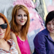 Girlfriends near graffiti wall. - Stok fotoğraf