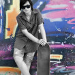 Style girl with skateboard near graffiti wall. - Stok fotoğraf