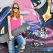 Style girl with skateboard near graffiti wall. — Stockfoto