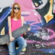 Style girl with skateboard near graffiti wall. — Photo