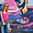 Style girl with skateboard near graffiti wall. — Foto Stock