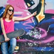 Style girl with skateboard near graffiti wall. — Stock fotografie