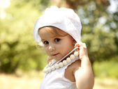 Cute little girl smiling in a park — Stock Photo