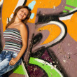 Beautiful brunette girl with guitar and graffiti wall at backgro — Stock Photo #6147639