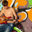 Royalty-Free Stock Photo: Beautiful brunette boy with guitar near graffiti wall.