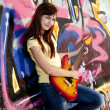 beautiful brunette girl with guitar and graffiti wall at backgro — Stock Photo