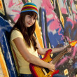 Stock Photo: Beautiful brunette girl with guitar and graffiti wall at backgro