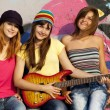 Three beautiful girls with guitar and graffiti wall at backgroun - Photo