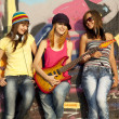 Stock Photo: three beautiful girls with guitar and graffiti wall at backgroun