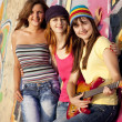 Three beautiful girls with guitar and graffiti wall at backgroun — Stock Photo