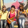 Three beautiful girls with guitar and graffiti wall at backgroun — Stock Photo #6147758