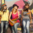 Foto Stock: Three beautiful girls with guitar and graffiti wall at backgroun
