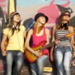 three beautiful girls with guitar and graffiti wall at backgroun — Stock Photo #6147765