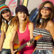 图库照片: Three beautiful girls with guitar and graffiti wall at backgroun