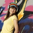 Beautiful brunette girl with headphones and graffiti wall at bac — Stock Photo #6147782