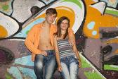 Beautiful couple with guitar near graffiti wall. — Stock fotografie